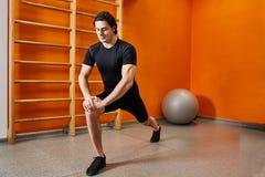 Forte giovane sportivo nello sportwear nero che allunga le gambe prima dell'allenamento della palestra Immagini Stock
