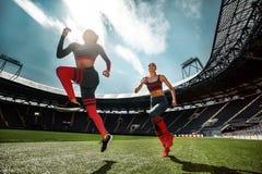Forte sprinter atletico della donna, corrente sullo stadio che dura in abiti sportivi Motivazione di sport e di forma fisica Conc immagini stock