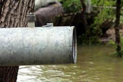 Forte tubo del metallo del grande diametro con la valvola di regolazione mancante sulla cima accanto al vecchio albero usato per  fotografia stock