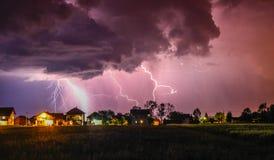 Forte tuono che colpisce casa con pioggia sopra la via del villaggio Fotografia Stock