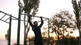 Forte, uomo adatto in vestiti neri di sport che fanno gli esercizi sulla barra orizzontale fuori nel campo sportivo nel parco stock footage