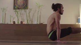 Forte uomo bello che fa gli esercizi di yoga video d archivio