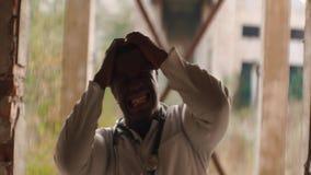 Forte uomo di colore arrabbiato che sta nel tunnel, prendente e schiacciante le sue mani, attrezzatura il suo testa, comprimente  stock footage