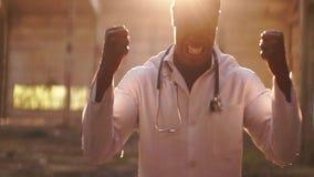 Forte uomo di colore arrabbiato che sta sulla luce del tramonto, alba, prendente e schiacciante le sue mani, attrezzatura il suo  stock footage