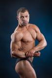 Forte uomo di misura che dimostra i suoi muscoli potenti Immagini Stock Libere da Diritti