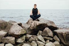 Forte uomo di yoga di forma fisica nella posa del loto sulla spiaggia della roccia vicino all'oceano Concetto armonico immagini stock libere da diritti