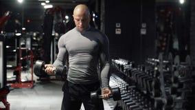 Forte uomo muscolare che fa gli esercizi di sport con le teste di legno, treni il bicipite, muscoli delle mani nella palestra scu video d archivio
