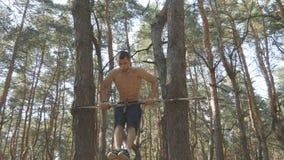 Forte uomo muscolare che fa un verticale sulla barra orizzontale in un tipo maschio muscolare di forma fisica della foresta che f Immagini Stock