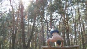 Forte uomo muscolare che fa un verticale in un tipo maschio muscolare di forma fisica della foresta che fa le acrobazie sul ceppo Fotografia Stock