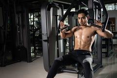 Forte uomo muscolare che prepara per l'allenamento nella palestra del crossfit Addestramento di pratica di inter-misura del giova immagine stock