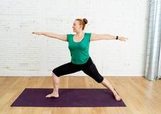 Forte yoga di addestramento della donna dentro a casa moderna dello studio nel concetto sano di stile di vita fotografie stock