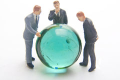 Fortelling the future. Miniature business men with marble Royalty Free Stock Photo