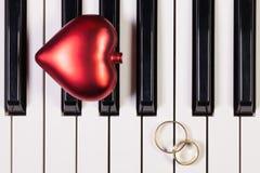 Fortepianowa klawiatura, czerwony serce i obrączki ślubne, Obraz Stock