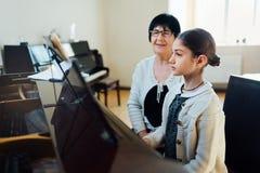 Fortepianowe lekcje przy muzyczną szkołą, nauczycielem i uczniem, obrazy royalty free