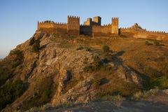 Fortezza che sta alta su una montagna ad alba Fotografie Stock Libere da Diritti