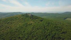 Fortezza medievale sulla cima delle colline in mezzo al terreno boscoso della montagna stock footage
