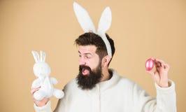 Fortfarande barnsligt Fira påsken Kanin för skäggig hipster för grabb gladlynt med långa vita öron easter kanin Bära för man royaltyfri bild