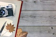 Fortfarande retro kamera, fotoalbum, penna och gulingsidor på trä Arkivfoto