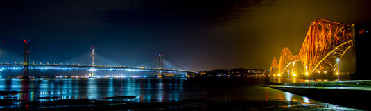 Forth Rail Bridge and Queensferry Crossing at night. The Forth Rail Bridge and Queensferry Crossing road bridge. Old and New. At night Stock Photo