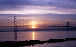 Forth Road Bridge at sunset. Forth Road Bridge near Edinburgh at sunset with the sun reflected in the River Forth stock photography