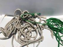 Forti le corde bianche e verdi della nave del tessuto, corde si trovano in un mucchio su una nave, barca su un fondo bianco fotografie stock