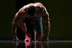 Forti uomini muscolari che si inginocchiano sul pavimento Immagine Stock