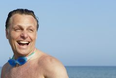 Forties man on beach. A handsome and happy forties man wearing swimming goggles around his neck is laughing as he enjoys a beautiful day at the beach Stock Image