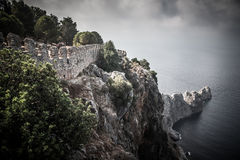 Fortification on the edge of a cliff into the sea leaving. drama Royalty Free Stock Image