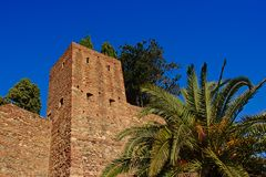 Fortifications of the Alcazaba moorish castle, Malaga. Surrounded by green plants on a sunny day with clear blue sky Royalty Free Stock Photos