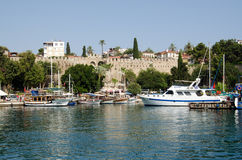 Fortifications, Antalya Harbour, Turkey. ANTALYA, TURKEY - AUGUST 18, 2014:  Fortifications of the medieval city of Antalya overlooking the harbour filled with Stock Photos