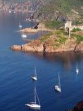 Fortificazione genovese di Girolata e della barca a vela Fotografia Stock Libera da Diritti