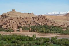 Fortified city of Ait Benhaddou along the former caravan route between the Sahara and Marrakech in Morocco with snow covered Atlas royalty free stock photos