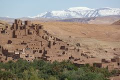 Fortified city of Ait Benhaddou along the former caravan route between the Sahara and Marrakech in Morocco with snow covered Atlas stock images