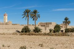 Fortified city of Erfoud along the former caravan route between the Sahara and Marrakech in Morocco with snow covered Atlas royalty free stock image