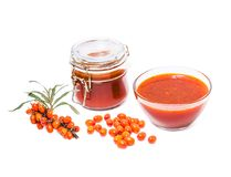 Fortified jam from fresh berries of sea buckthorn mashed with su. Gar in a glass jar, vase with jam, the berries on the branch and berries in bulk on white stock photo