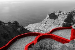 Fortified red wall of the medieval castle. Beautiful scenic view of the country house on the mountain and the blue sea. Panoramic. Sea view. Black and white royalty free stock photo