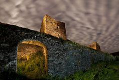 Fortified wall and castle towers in ruins under cloudy night sky. Defensive rectangle old medieval towers under  cloudy night sky. The kingdom of leon in Spain stock images