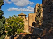 Fortified walls and towers of the Alcazaba moorish castle, Malaga. Fortified brick walls and towers of the Alcazaba moorish castle, Malaga,  on a sunny day with Royalty Free Stock Photography