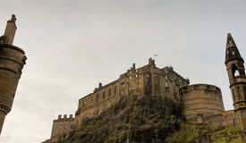 Fortifique a rocha e o castelo de Edimburgo, vistos de baixo de e moldados por uma chaminé e por um pináculo Fotos de Stock Royalty Free
