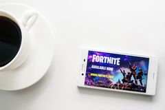 Ufa, Russia - March 15, 2019: Fortnite game on Android smartphone screen, phone and coffee cup on white background, copy space. Fortnite game on Android royalty free stock image
