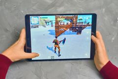 Fortnite Gameplay on ipad. Bishkek, Kyrgyzstan - January 21, 2019: Woman playing fortnite game of epic games company on Apple ios tablet iPad Pro stock images