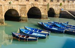 Fortress and blue fishing boats in Essaouira. View of Old Fortress Sqala du Port and blue fishing boats in Essaouira. Morocco Royalty Free Stock Photo
