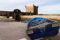 The fortress of Castelo Real of Mogador and blue fishing boata a Royalty Free Stock Photo