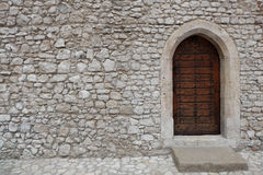 Fortress or castle wall made of stacked stone blocks and a wooden door with gothic style pointed arch. The brown wooden back door or entrance to an old building Stock Photos