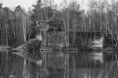 Fortress conquered by nature. Old fortress conquered by nature reflecting on the water in black and white Royalty Free Stock Photography
