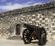 Fortress entrance and iron cannon. Wheel cannon close to a pillbox vintage door Royalty Free Stock Photos
