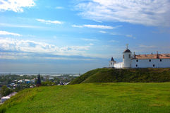 Fortress on the hill. View of the fortress on the hill and town in the valley on background of cloudy blue sky Stock Photography