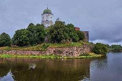 Fortress on the island. Russia, Leningrad region,. View of the fortress in the city of Vyborg from the opposite shore, Russia, Leningrad region, noon, sun at its Stock Photos