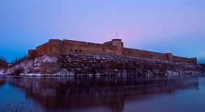 Fortress of Ivangorod by twilight. View of the fortress of Ivangorod and Narva river by twilight Stock Image