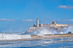 The fortress and lighthouse of El Morro in Havana with sea waves crshing on the seawall Stock Photos